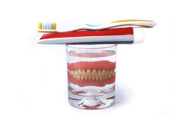 Eine Zahnprothese der Zahnarztpraxis Jguburia im Wasserglas